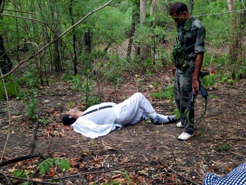 A security personnel stands near the body of one of the victims of Maoist attack in a densely forested area in Bastar, about 345 kilometers (215 miles) south of Raipur, Chhattisgarh. AP Photo
