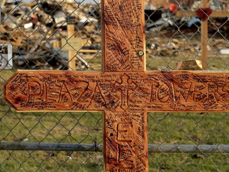 Messages are written on a cross at a makeshift memorial outside Plaza Towers Elementary School which was destroyed by a tornado nearly a week ago in Moore, Oklahoma. AP