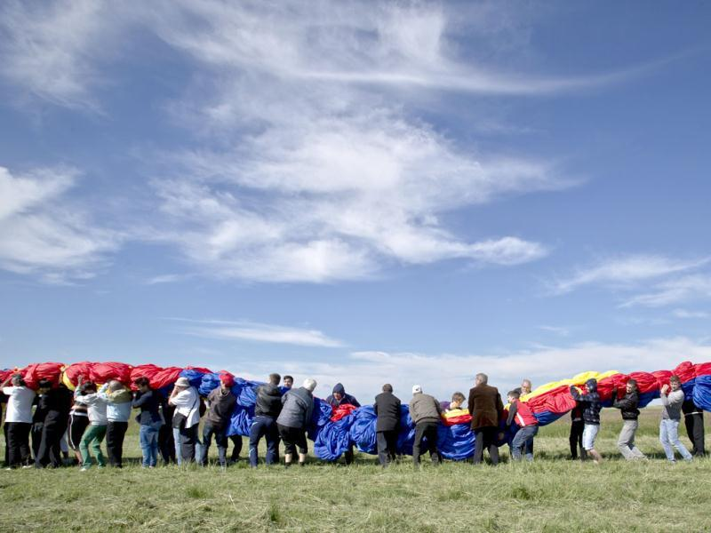 Romanians carry a huge national flag on the Clinceni Airfield, south of Bucharest, Romania. (AP)