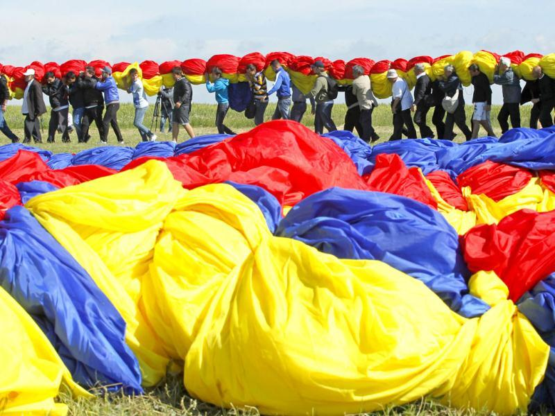 Workers carry Romania's national flag during a Guinness World Record attempt for the world's biggest national flag in Clinceni, near Bucharest. (Reuters)