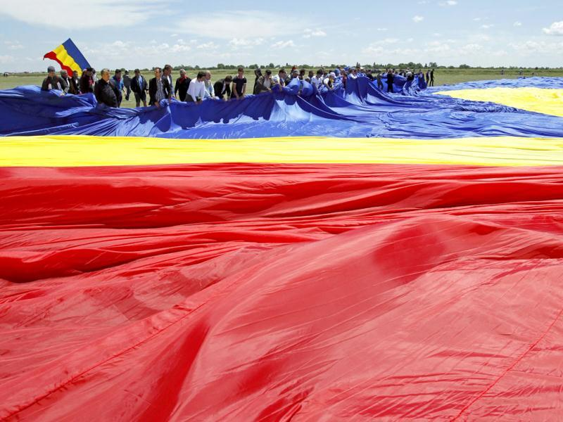 Workers arrange Romania's national flag during a Guinness World Record attempt for the world's biggest national flag in Clinceni. (Reuters)