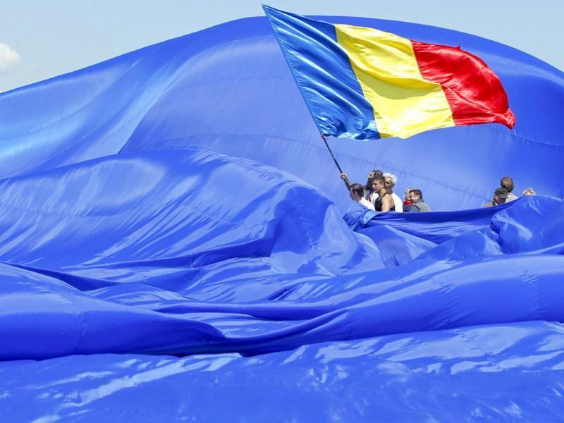 Workers arrange Romania's national flag during a Guinness World Record attempt for the world's biggest national flag in Clincen. (Reuters)