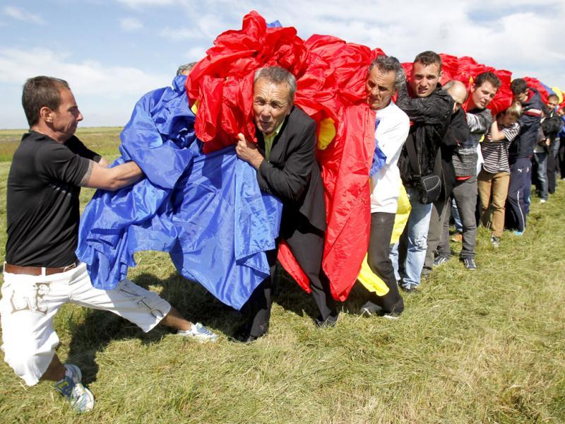 Workers carry Romania's national flag during a Guinness World Record attempt for the world's biggest national flag in Clinceni, near Bucharest. The flag, measuring 349.4 per 226.9 meters, established a new Guinness World Record. (Reuters)