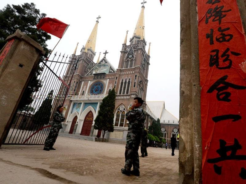 Security guards keep a watch over Chinese Catholics who belong to an