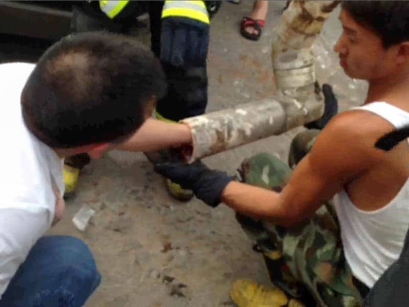 This frame grab taken from AFPTV footage shows a rescue worker reaching into a pipe after an abandoned newborn baby was found inside in the city of Jinhua, in the eastern province of Zhejiang. AFP photo/AFPTV