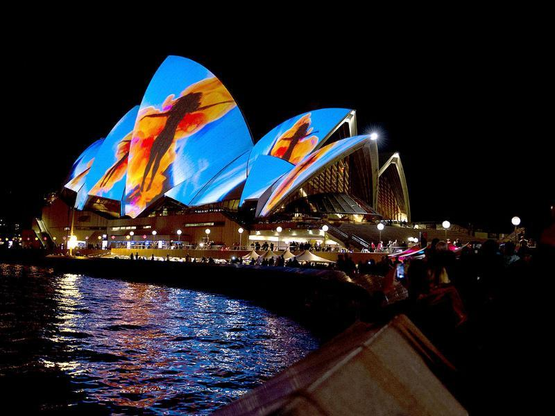 Visitors look at the Opera House being lit up by a projection during Vivid Sydney, the annual festival of light, music and ideas, in Sydney. AFP PHOTO