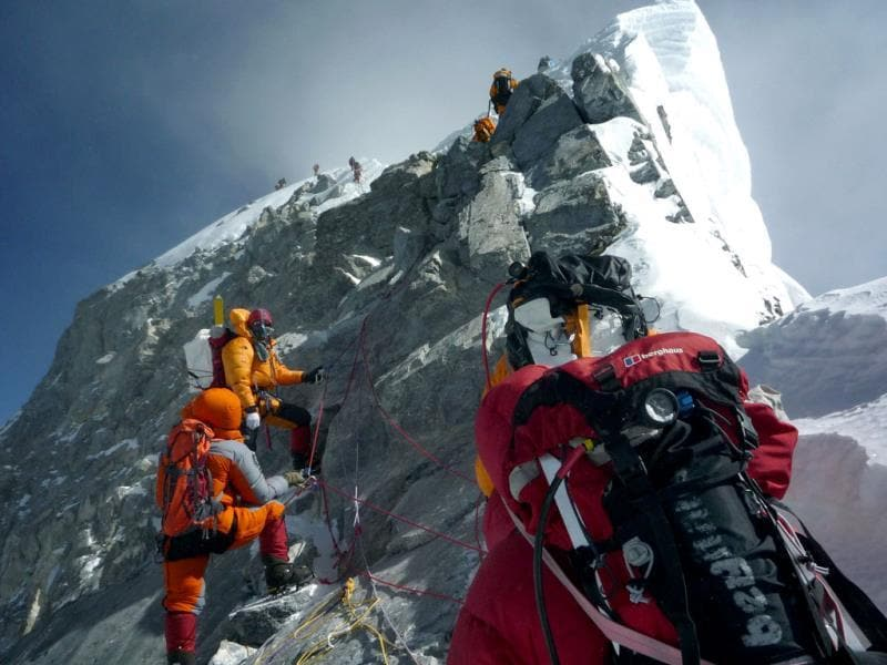 In this file photograph taken on May 19, 2009, unidentified mountaineers walk past the Hillary Step while pushing for the summit of Everest as they climb the south face from Nepal. AFP PHOTO
