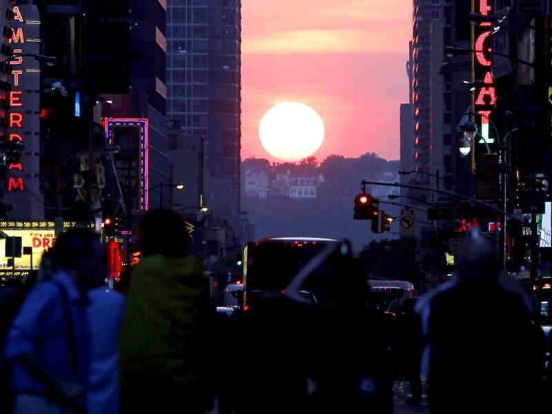 The sun shines down 42nd Street at sunset during the biannual occurrence named