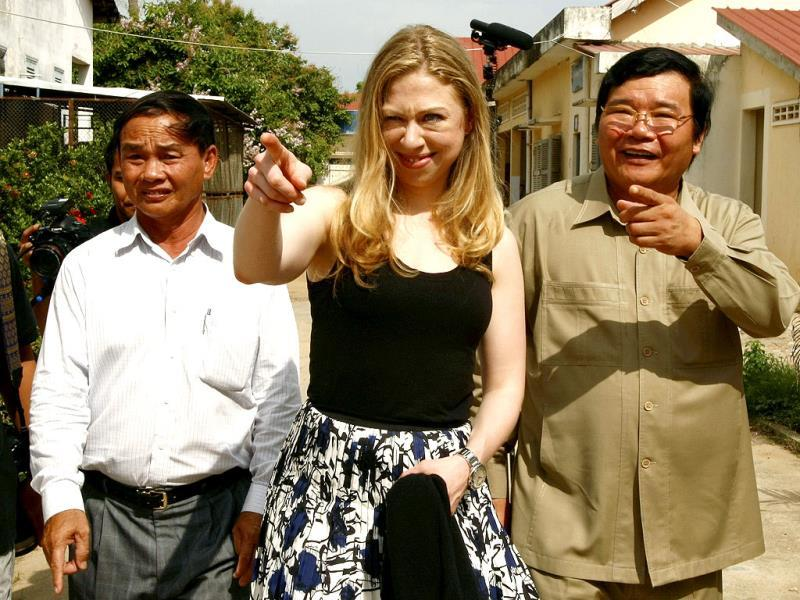 Chelsea Clinton, center, daughter of former US President Bill Clinton, gestures as she tours with Cambodian Dr. Mean Chhi Von, right, director of the National Center of HIV/AIDS, in Neak Loeung town, Prey Veng province, about 63 kilometers (39 miles) east of Phnom Penh, Cambodia. AP photo