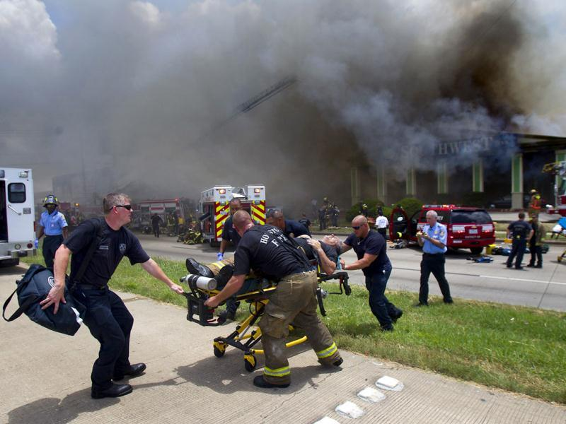 A firefighter is wheeled to an ambulance after fighting a fire at the Southwest Inn in Houston. (AP)