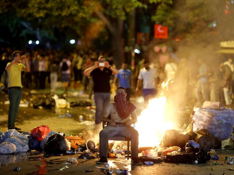 An anti-government protester sits in front of rubbish set on fire by protesters as they clash with riot police in central Ankara. (Reuters)