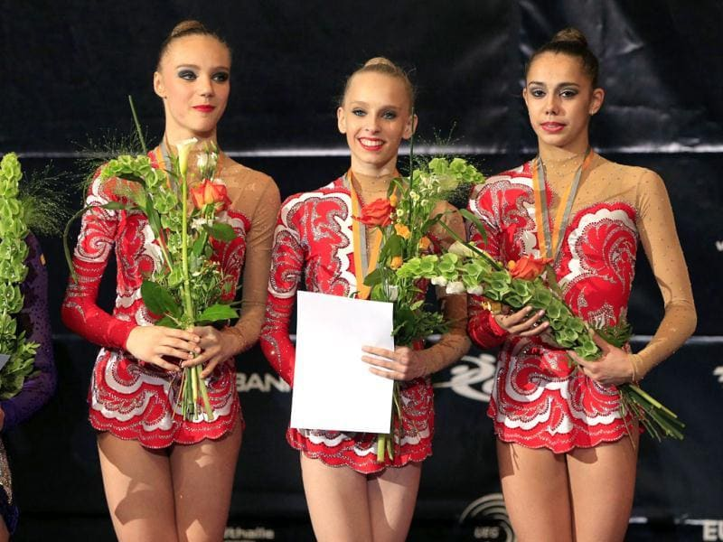 (L-R) Daria Svatkovskaya, Yana Kudryavtseva, Margarita Mamum pose on the podium after competing in the senior individual team competition as part of the 29th rythmic gymnastics European Championships held at the Stadthalle in Vienna. (AFP)
