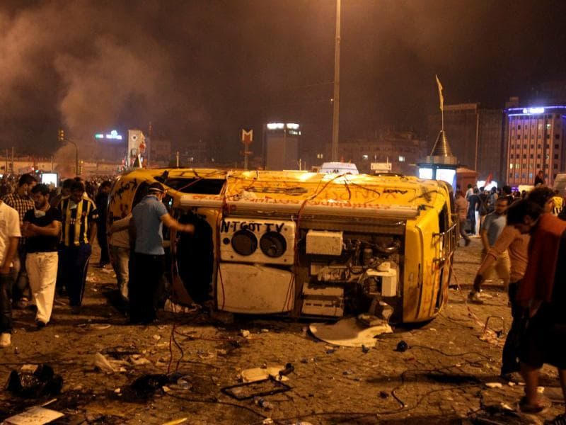 Protesters look a destroyed car during a rally at the Taskim square in Istanbul. (AP)