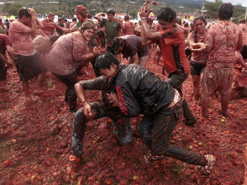 Revellers play with tomato pulp during the annual