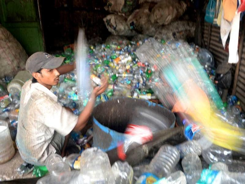 A man sorts out used plastic bottles for recycling at a roadside unit in Mumbai on the eve of World Environment Day. AFP Photo