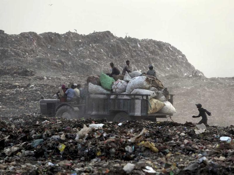 A young ragpicker runs after a truck carrying sacks of garbage at a dumpyard in New Delhi. AP Photo