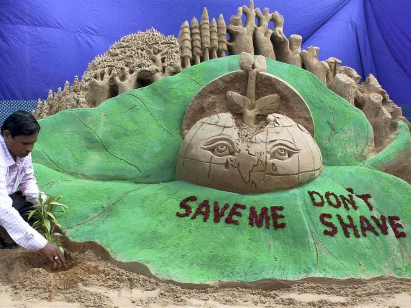 Sand artist Subal Maharana gives a finishing touch on a sand sculpture on eve of World environment day in Bhubaneswar. PTI Photo