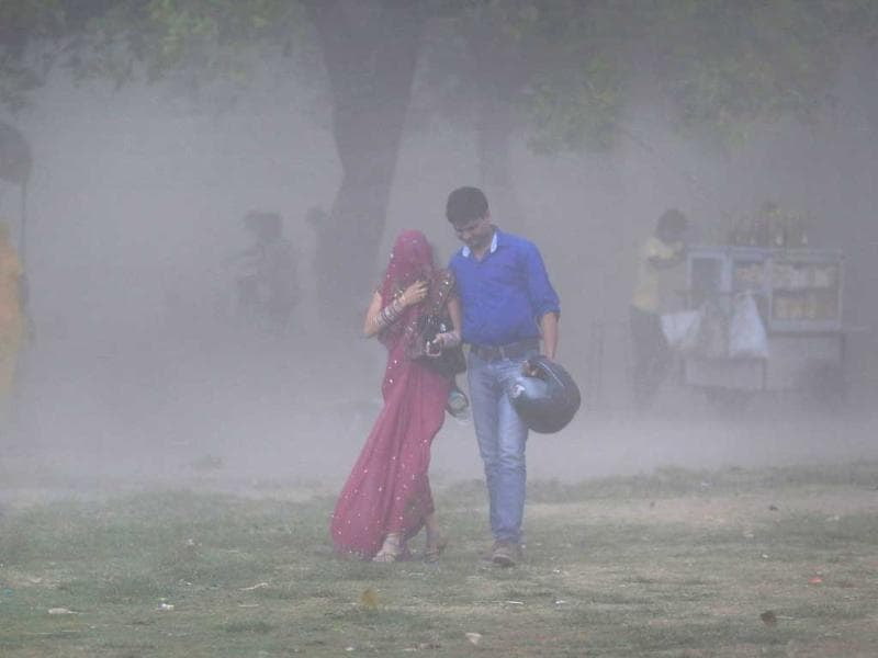 A couple walks through a sandstorm as they enjoy an evening out Delhi. Rain and strong winds lashed the capital, bringing some much needed relief to the people. (AP)