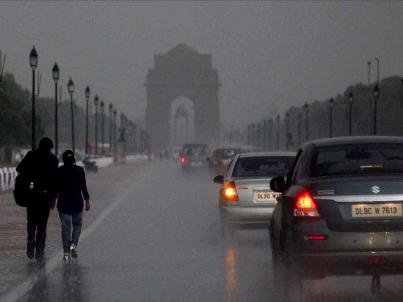 A couple walks along Rajpath near India Gate as rain brought Delhi some much needed respite from rising temperatures. (PTI)