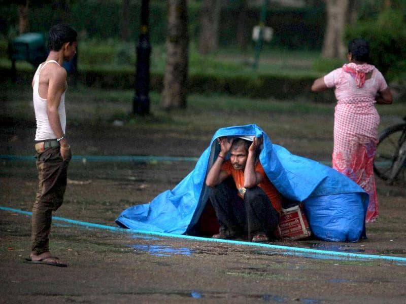 A vendor shields himself with a plastic sheet near India Gate during heavy rain in New Delhi. Rain and strong winds lashed the capital bringing a much needed decrease in Delhi's temperatures. (PTI)