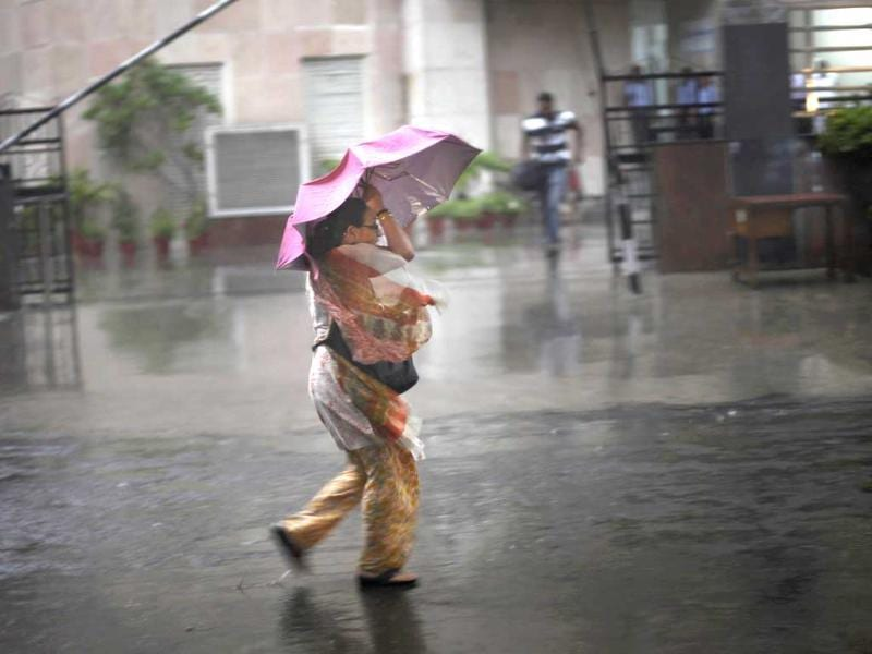 A woman struggles with her umbrella against a strong wind during a sudden heavy downpour in New Delhi. Rain lashed the capital, bringing in much some needed relief to Delhiites. (AP)
