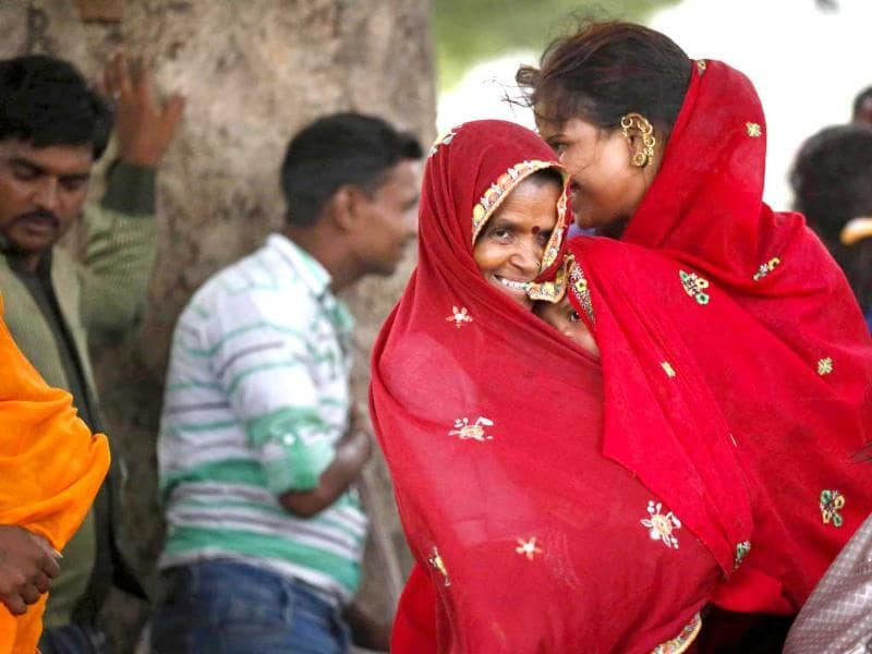 A women protects her child from blowing sand as they stand under a tree during a sandstorm in Delhi. Rain and strong winds lashed the capital and brought in some much needed relief to the people. (AP)