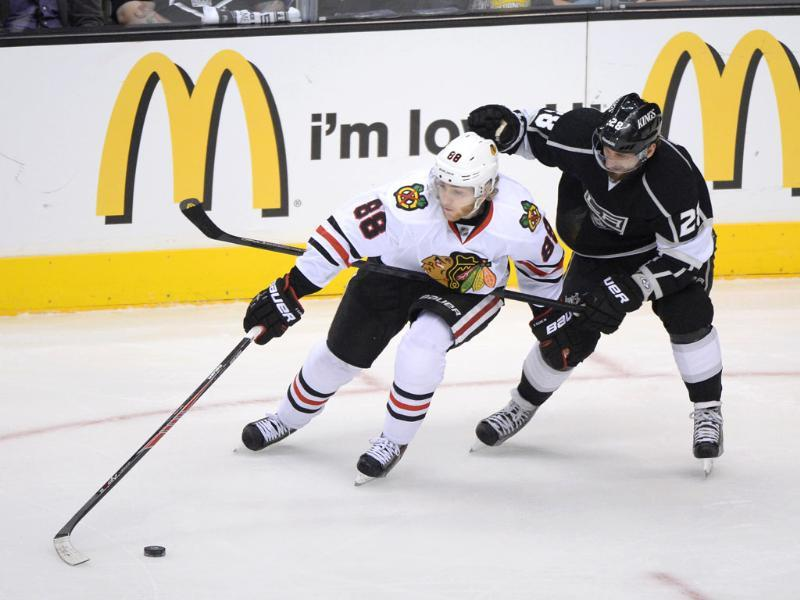 Patrick Kane of the Chicago Blackhawks plays the puck while under pressure from Jarret Stoll of the Los Angeles Kings in the first period of Game Four of the Western Conference Final during the 2013 NHL Stanley Cup Playoffs at Staples Center in Los Angeles, California. AFP/Getty Images