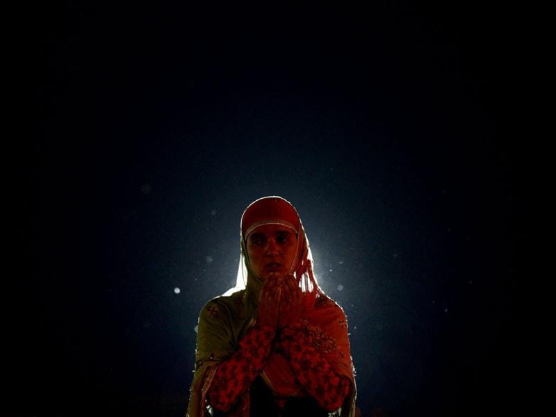 A Kashmiri Muslim woman praying during Miraj-Ul-Alam celebrations