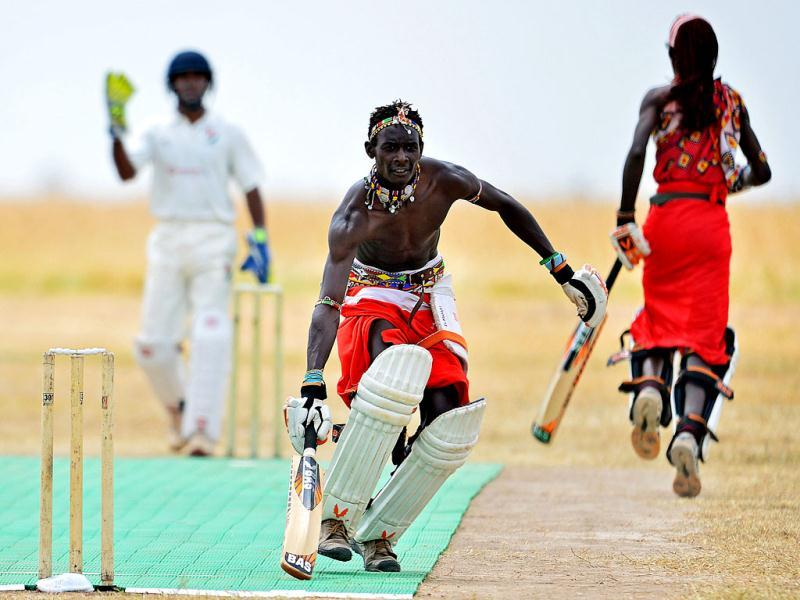 A Maasai batsman scores runs as the Maasai Warriors cricket team play a Twenty twenty match against international cricket team the Abassadors, in Ol Pejeta conservency in Laikipia national park. AFP PHOTO