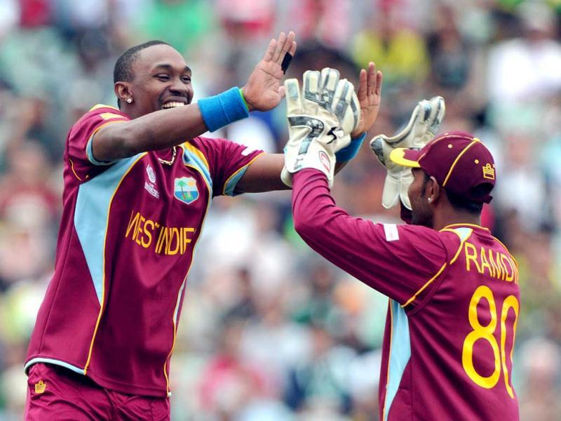 Dwayne Bravo (L) celebrates after running out Pakistan's Wahab Riaz during the 2013 ICC Champions Trophy cricket match between Pakistan and West Indies at The Oval cricket ground in London. (AFP)