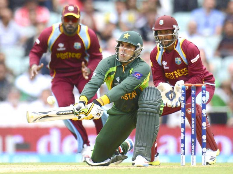 Misbah-Ul-Haq plays a reverse sweep as West Indies' Chris Gayle and Denesh Ramdin (R) look on during the ICC Champions Trophy group B match at The Oval cricket ground in London. (Reuters)
