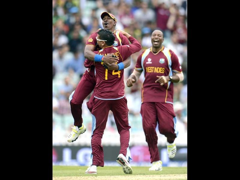 Dwayne Bravo leaps on teammate Sunil Narine as Kieron Pollard (R) looks on after the dismissal of Pakistan's Kamran Akmal during the ICC Champions Trophy group B match at The Oval cricket ground, London. (Reuters)