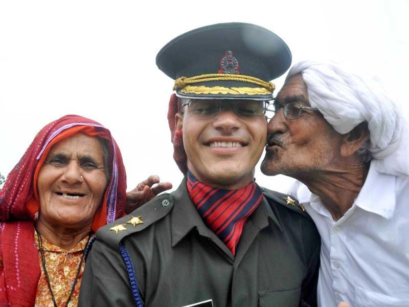 A newly commissioned officer with his parents during the passing out parade at the Indian Military Academy in Dehradun. PTI Photo