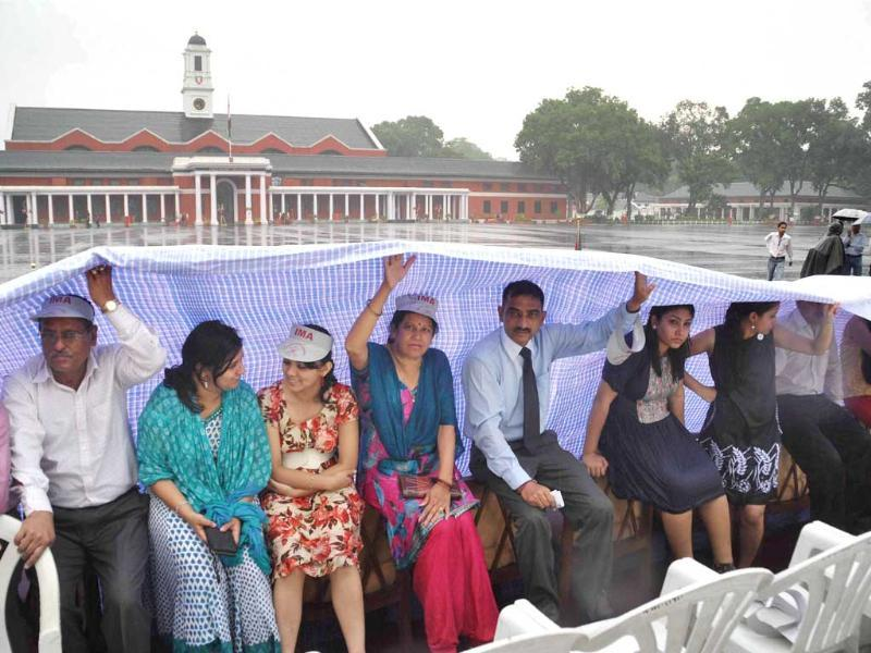 Family members of cadets cover themselves with a sheet as it rains during the passing out parade at the Indian Military Academy in Dehradun. PTI Photo