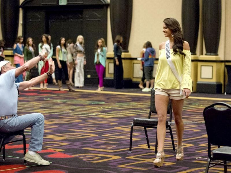In this photo provided by the Miss Universe Organization, Miss Georgia USA 2013 Brittany Sharp rehearses for the upcoming 2013 Miss USA Competition with Stage Manager Kenny Stein in Las Vegas. AP