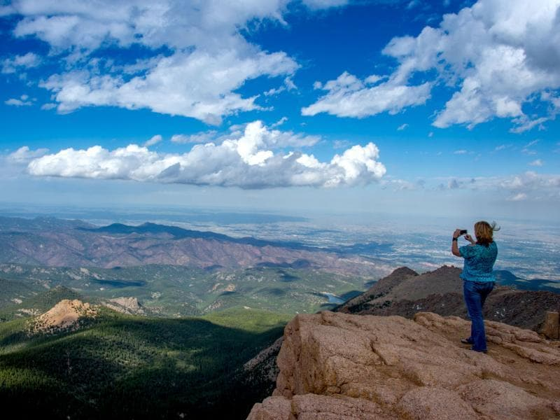 A woman takes a picture at the top of Pikes Peak mountain in the Front Range of the Rocky Mountains within Pike National Forest, 10 miles (16 km) west of Colorado Springs, Colorado. AFP