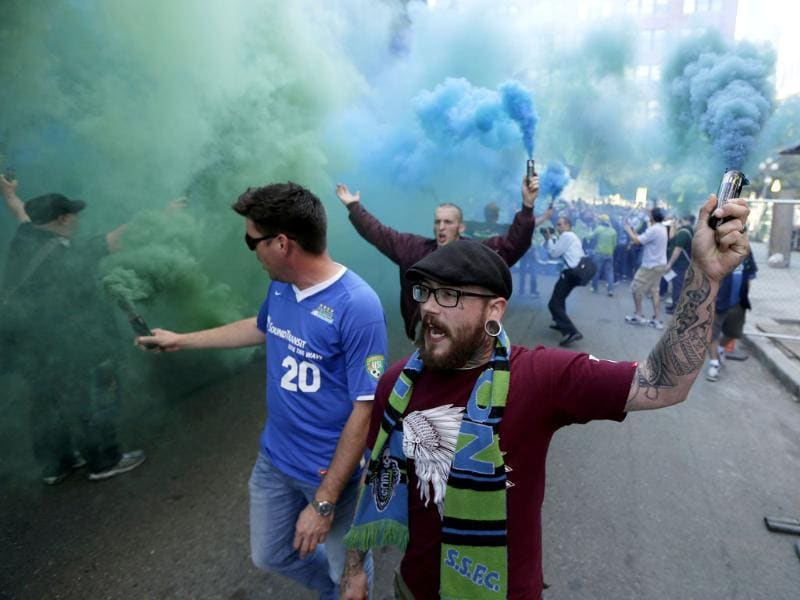 Seattle Sounders supporters carry blue and green smoke effects as they take part in the traditional