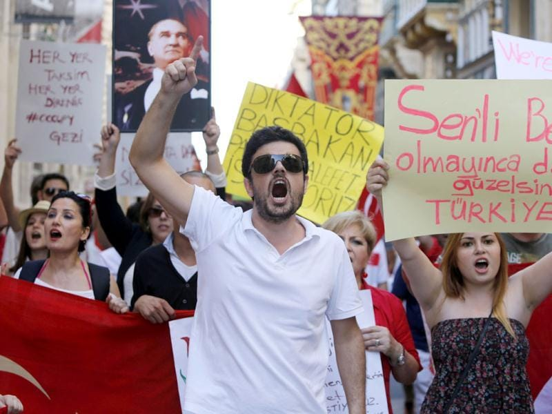 Members of the Turkish community living in Malta shout slogans during a peaceful protest in solidarity with their compatriots in Turkey in Valletta