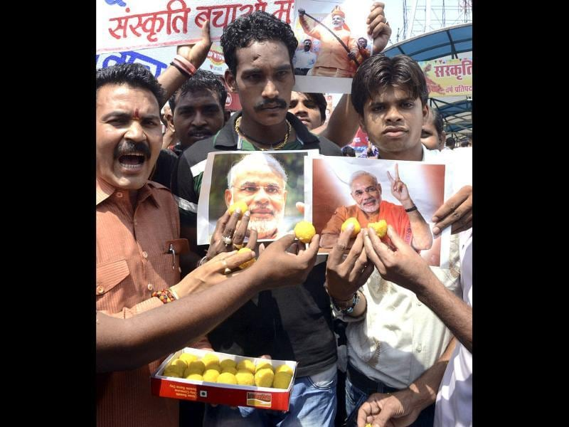 Supporters celebrate as they hold photographs of BJP's new 2014 election campaign head Narendra Modi in Bhopal. AP Photo