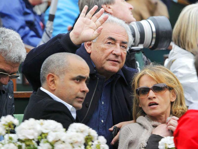 Former International Monetary Fund (IMF) chief Dominique Strauss-Kahn (C) and Myriam L'Aouffir (R) watch the men's singles final match between Rafael Nadal and David Ferrer at the French Open tennis tournament at the Roland Garros stadium in Paris. Reuters