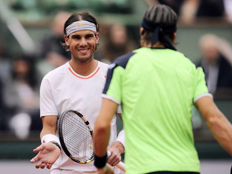 Rafael Nadal smiles at compatriot David Ferrer as they arrive for their men's singles final match at the French Open tennis tournament in Paris. Reuters