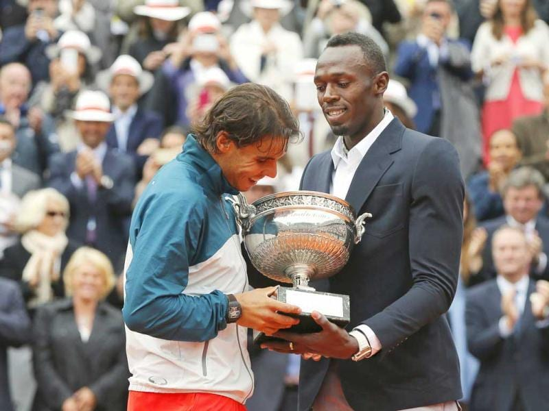 Rafael Nadal receives the trophy from Jamaican sprinter Usain Bolt after defeating David Ferrer in their men's singles final match to win the French Open final in Paris. Reuters