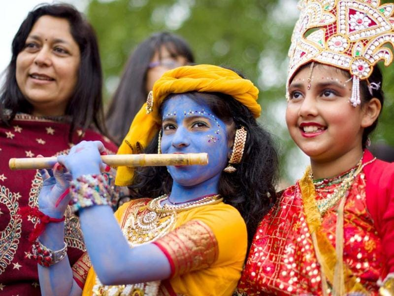 Children dressed in costumes, representing Lord Krishna and Radha, pose for a photograph during the