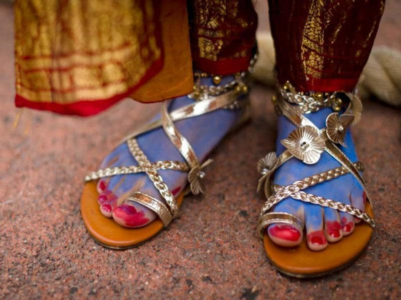 The feet of a devotee wearing a costume representing Lord Krishna during the