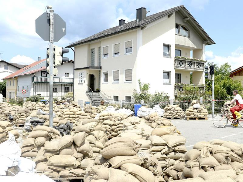A local resident cycles past sand bags in a street that was hit by the floods of the river Danube in Fischerdorf near Deggendorf, southern Germany. AFP