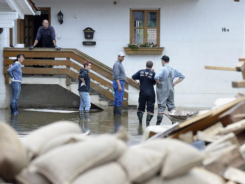 Local residents stand in front of a house that was hit by the floods of the river Danube in Fischerdorf near Deggendorf, southern Germany. AFP