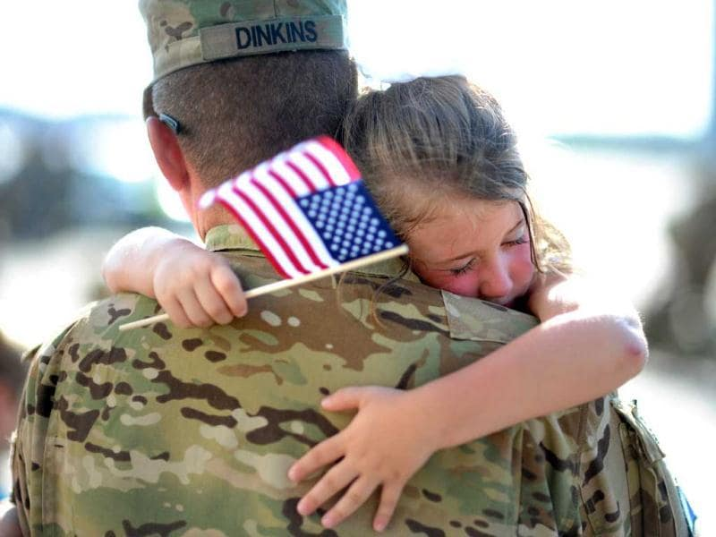 US Army Staff Sgt. Jason Dinkins with the 3rd Combat Aviation Brigade is hugged by his daughter Olivia Chastain after a welcome home ceremony at Hunter Army Airfield in Savannah. (AP)
