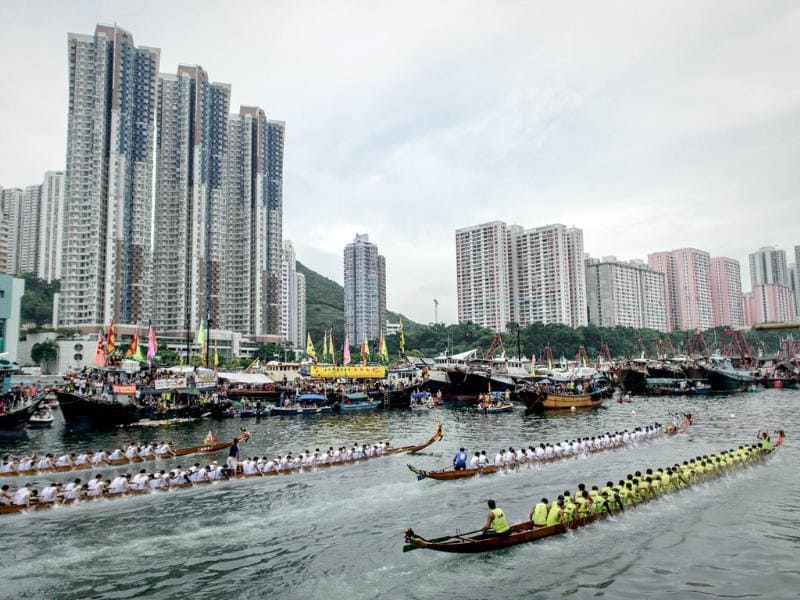 Competitors paddle past high rise residential buildings during the dragon boat festival in Hong Kong. AFP