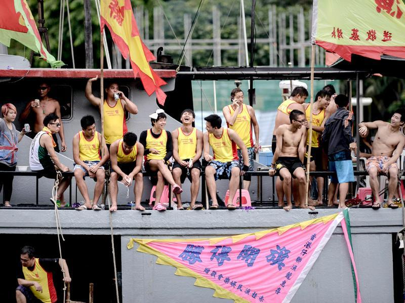 Supporters and team members stand on boats as they watch the dragon boat festival in Hong Kong. AFP