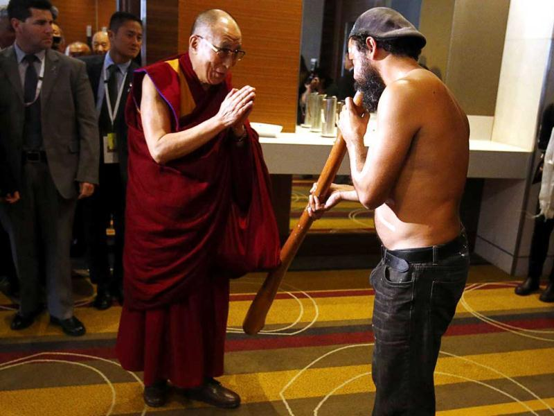 An Australian Aboriginal man plays a wooden wind instrument known as a didgeridoo as the Tibetan spiritual leader the Dalai Lama arrives at a media conference in Sydney. (Reuters)